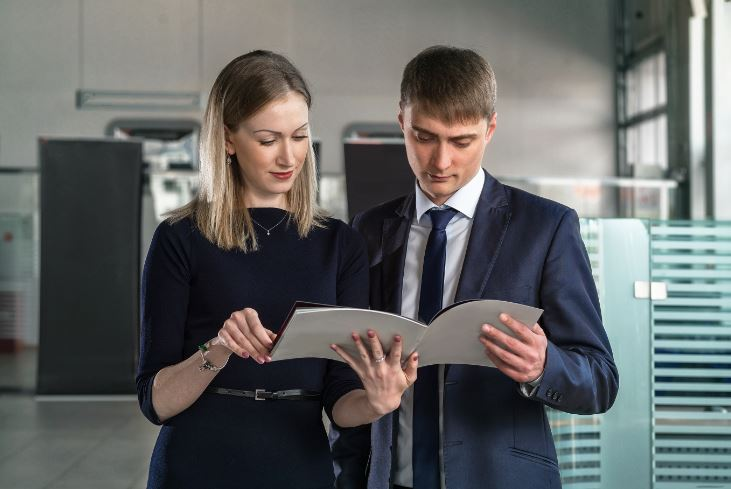 young business man and woman impressed by printed brochure
